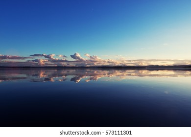 Clouds in the distance mirrored in the deep blue , calm water of a lake in Oregon.
