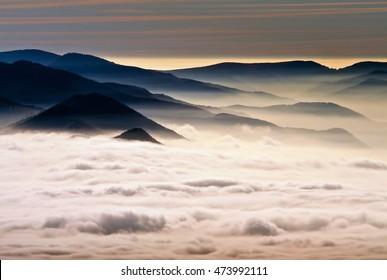 雲が山の水平の下で谷間に垂れ下がった。嵐の雲の上の日の出。