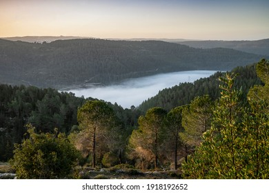 Clouds fill a valley among the Judea mountains near Jerusalem, Israel, on a clear winter day.