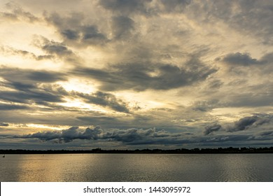 The clouds filled the sky, obscuring the light from the sun during the sunset. The sky on the top is coloured orange from the sun. The bottom sky is black and gray from the rain clouds.