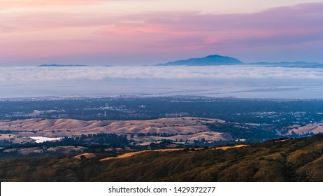 Clouds and fog at twilight over Silicon Valley and the San Francisco bay area; Stanford University visible under a layer of clouds; Mt Diablo in the background;