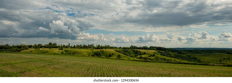 clouds forest and meadows in hilly terrain, rural panoramic landscape. Spring season. Banner for design.