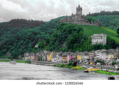 Clouds gathering over Cochem castle, perched on the bank of the river Moselle, Germany. The castle has vineyards right in front, winding down to the quaint center of Cochem town