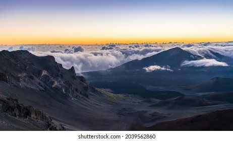 Clouds hang on jagged volcanic peaks during a dramatic morning sunrise in Haleakala National Park on the island of Maui, Hawaii.