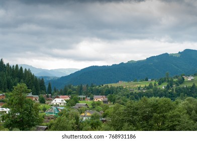 Clouds have gathered over a mountain village in Carpahia. Houses are surrounded by trees. A nice place for recreation and holidays in Ukraine.