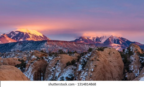 Clouds illuminated by bounce light off the snow on the LaSal peaks at sunset, seen from the Sand Flats Recreation Area in Moab, Utah.
