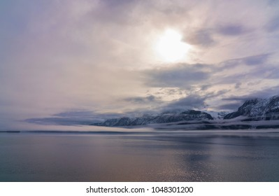 Clouds and low fog clearing to reveal mountains on a calm evening on the Chilkat Inlet near Haines, Alaska.
