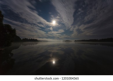 Clouds in the night over the lake lit by full moon, long exposure shot