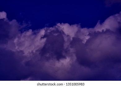Clouds in the night sky lighted by the moon. Abstract nature background.