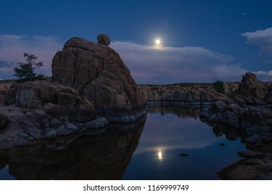 Clouds obscured the full moon rise yet later offered a view with reflection among the boulders around Watson Lake in Prescott, Arizona.