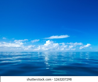 clouds on blue sky over calm sea with sunlight reflection