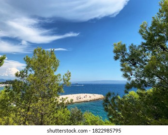 clouds over a beach in Split, Croatia with green trees