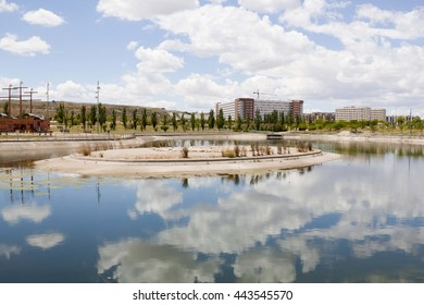 clouds over a lake, a park and an urbanization in Zaragoza
