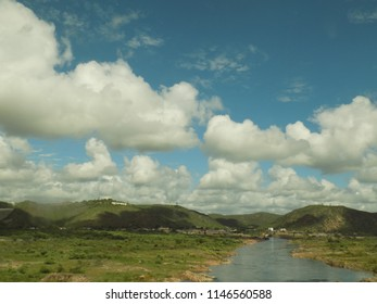 Clouds over river with mountains in background
