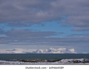 Clouds over the snow-covered mountains on the coast of Iceland