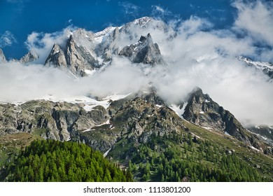 clouds over the top of the mountains of Mont Blanc Group Aosta Valley in spring season with blue sky in background