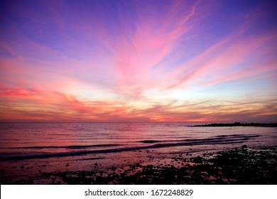 Clouds radiate red like fireworks against a purple sky from the post glow of a sunset, mirrored I the calm waters of the Gulf of Mexico on the west coast of Florida.