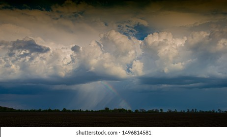 Clouds and Rain with Rainbow Evening in May, Landscape. Spring Season. Web banner.