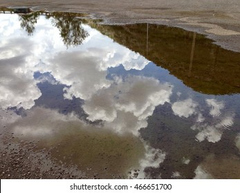 Clouds reflect in a puddle