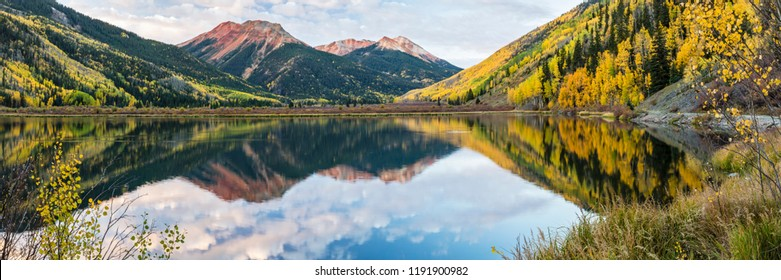 Clouds reflected in Crystal Lake below the Red Mountains in Autumn in the Uncompahgre National Forest south of Ouray, Colorado. (panorama)