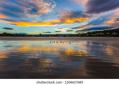 Clouds are reflected in the gentle ripples of the surf. Sunset on the Pacific coast, New Zealand. The concept of active and ecotouris