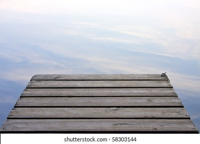 Clouds reflected in the lake at the end of a wooden pier