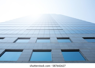 Clouds reflected and sunlight in windows of modern office building.