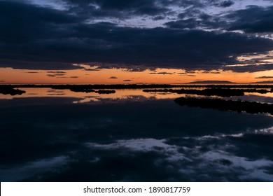 Nubes reflectantes en el agua tranquila después de la puesta de sol