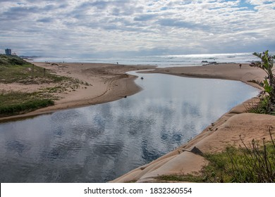 Clouds reflecting on river flowing into the sea