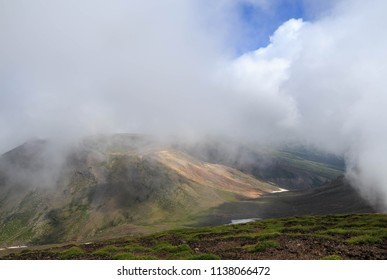 Clouds sail over valley below peak of Mt. Asahi in summer