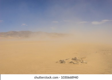 Clouds of sand blow around rocks in the midst of a vast sand desert.