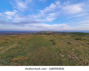 Clouds seem to stretch and race away from the centre of the bright blue sky above rolling English hills. The grass of the South Downs stretches outwards, away from us, as far as the eye can imagine.