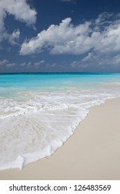 Clouds and sky meet warm, clear water and white sand in the Caribbean Sea.