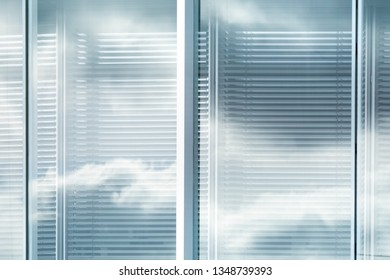 Clouds and sky reflected in windows with louvers of modern office building in city, blurred effect