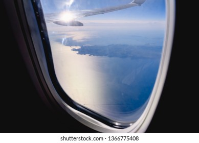 Clouds and sky seen through the window of an airplane, airplane travel concept.