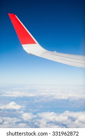 Clouds and sky as seen through window of an aircraft. Wing of the plane on sky background