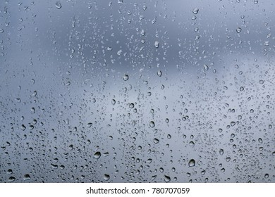Clouds in the sky through the window glass in drops of water during autumn rain. Toned blue