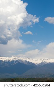 clouds, snow-capped mountains in the background of white clouds and blue sky
