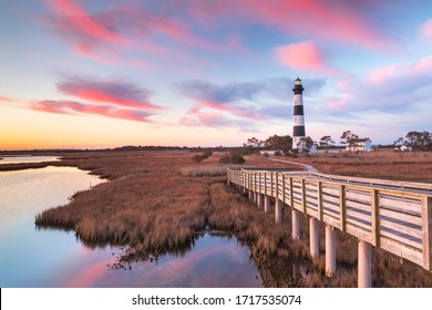 Clouds stream like pink ribbons in the sky over the marsh and lighthouse on Bodie Island on the Outer Banks of North Carolina.