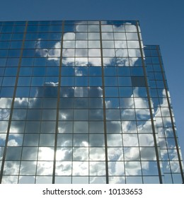 Clouds & sun reflected in windows of office building