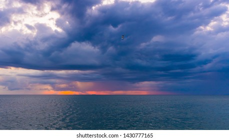Clouds at sunset sky over ocean, sea water. Red, Orange sunlight at horizon. Beautiful summer nature background