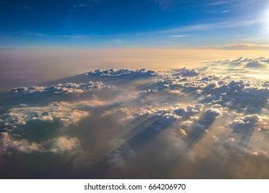 Clouds and sunset sky as seen through window of an aircraft.
