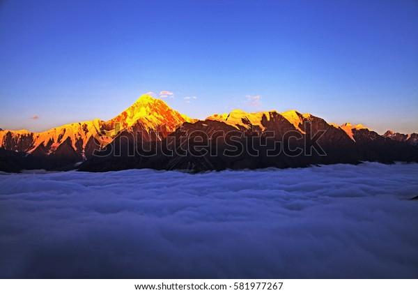 clouds surround  snow mountain  peak during sunrise