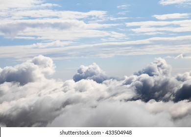 Cloudscape with an aerial view over the white cumulus cloud formations under a blue sky
