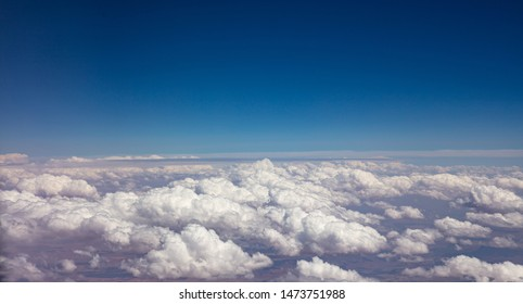 Cloudscape background. Blue sky and fluffy clouds Aerial view out of an airplane window.