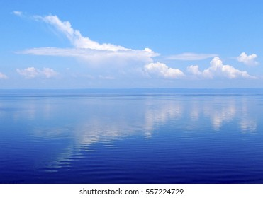 Cloudscape, big white cloud and reflection in water, clouds over lake Baikal, Russia