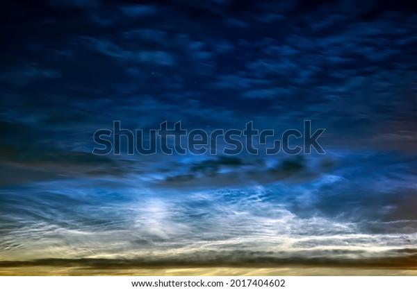 Cloudscape of illuminating, aka noctilucent  night clouds in dark blue sky.