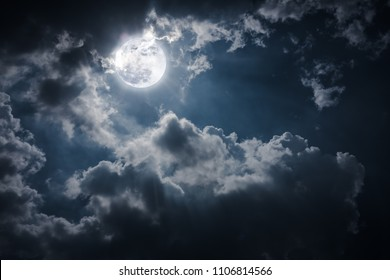 Cloudscape at nighttime. Night landscape of sky with dark clouds and bright full moon, serenity nature background. The moon were NOT furnished by NASA.
