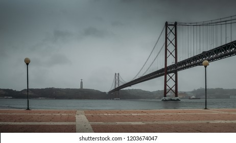Cloudscape view of 25 April Bridge on River Tagus and Christ the King monument in Lisbon, Portugal.