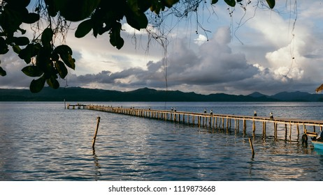 Cloudscape with wooden pier in kri island before tropical thunderstorm. Raja Ampat archipelago, West papua, Indonesia